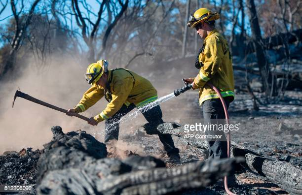 Bryce Briare and Mike Manibusan with the Marin County Fire Deptartment work on a smoldering hotspot as firefighters continue to build towards...