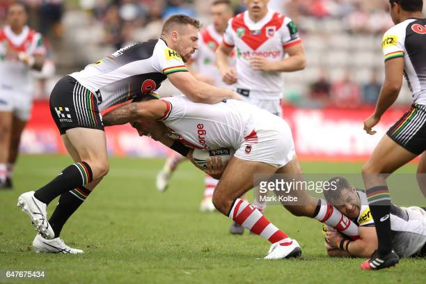 Bryce Cartwright and Trent Merrin of the Panthers tackle Paul Vaughan of the Dragons during the round one NRL match between the St George Illawarra...
