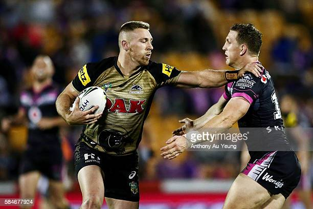 Bryce Cartwright of the Panthers fends against Ryan Hoffman of the Warriors during the round 21 NRL match between the New Zealand Warriors and the...