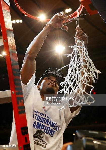 Bryce Cotton of the Providence Friars cuts down the net as he celebrates their 65 to 58 win over the Creighton Bluejays during the Championship game...