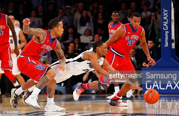 Bryce Cotton of the Providence Friars in action against D'Angelo Harrison and Orlando Sanchez of the St John's Red Storm during the quarterfinals of...