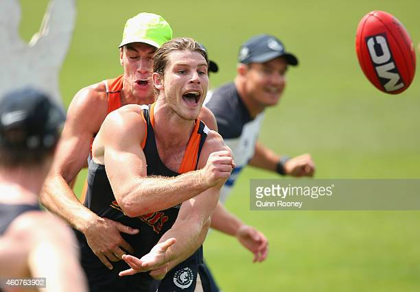 Bryce Gibbs of the Blues handballs whilst being tackled by Matthew Kreuzer during a Carlton Blues AFL Training session at Visy Park on December 22...