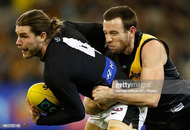 Bryce Gibbs of the Blues is tackled by Jake Batchelor of the Tigers during the 2015 AFL round 15 match between the Richmond Tigers and the Carlton...