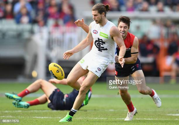 Bryce Gibbs of the Blues kicks whilst being tackled by Alex NealBullen of the Demons during the round two AFL match between the Melbourne Demons and...