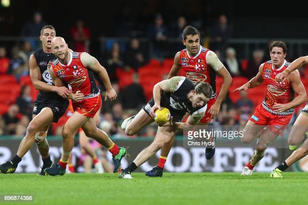 Bryce Gibbs of the Blues runs the ball during the round 13 AFL match between the Gold Coast Suns and the Carlton Blues at Metricon Stadium on June 17...