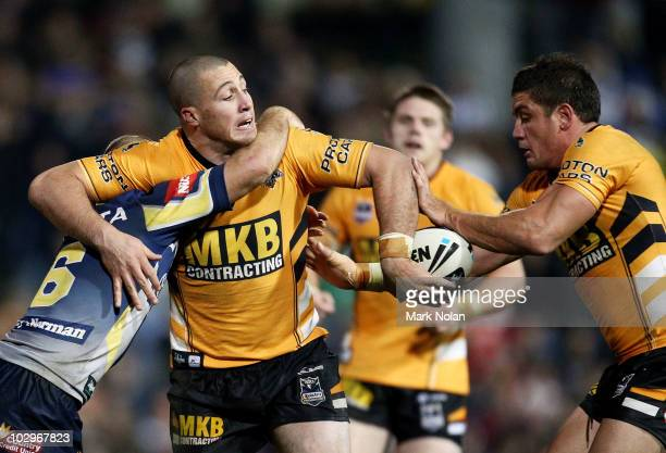 Bryce Gibbs of the Tigers offloads to Chris Heighington during the round 19 NRL match between the Wests Tigers and the North Queensland Cowboys at...
