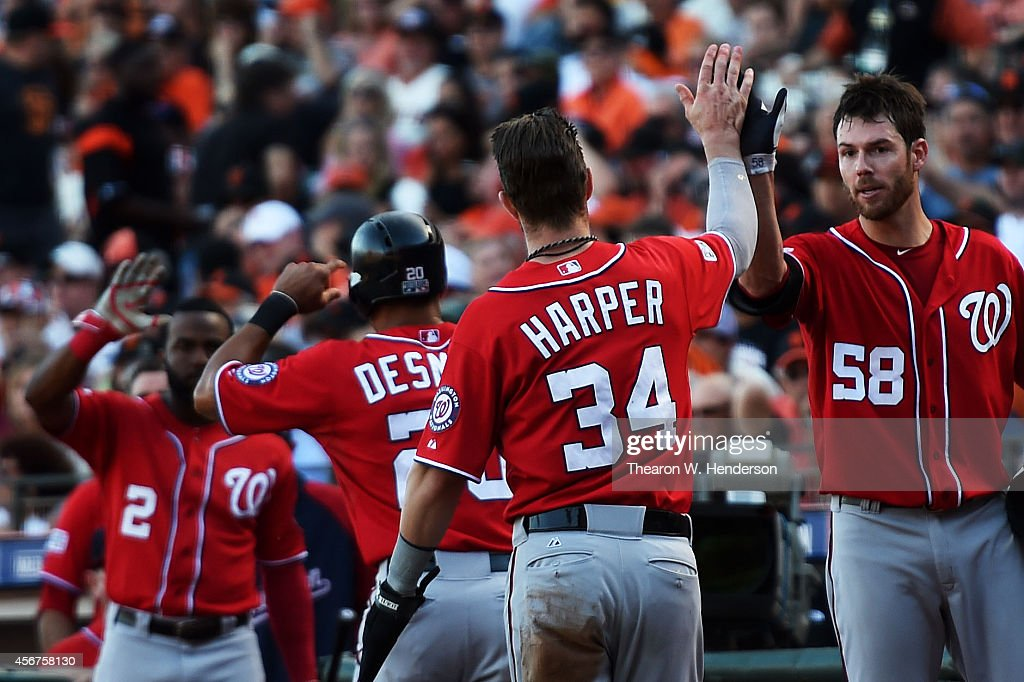 <a gi-track='captionPersonalityLinkClicked' href=/galleries/search?phrase=Bryce+Harper&family=editorial&specificpeople=5926486 ng-click='$event.stopPropagation()'>Bryce Harper</a> #34 and <a gi-track='captionPersonalityLinkClicked' href=/galleries/search?phrase=Ian+Desmond&family=editorial&specificpeople=835572 ng-click='$event.stopPropagation()'>Ian Desmond</a> #20 of the Washington Nationals celebrate with teammates <a gi-track='captionPersonalityLinkClicked' href=/galleries/search?phrase=Doug+Fister&family=editorial&specificpeople=6144840 ng-click='$event.stopPropagation()'>Doug Fister</a> #58 and <a gi-track='captionPersonalityLinkClicked' href=/galleries/search?phrase=Denard+Span&family=editorial&specificpeople=835844 ng-click='$event.stopPropagation()'>Denard Span</a> #2 after they scored in the seventh inning against the San Francisco Giants during Game Three of the National League Division Series at AT&T Park on October 6, 2014 in San Francisco, California.