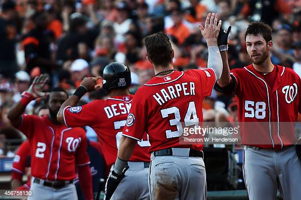 Bryce Harper and Ian Desmond of the Washington Nationals celebrate with teammates Doug Fister and Denard Span after they scored in the seventh inning...
