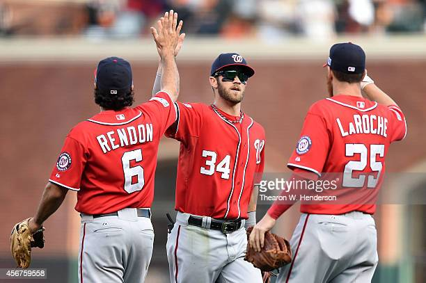 Bryce Harper celebrates with Anthony Rendon and Adam LaRoche of the Washington Nationals after their 4 to 1 win over the San Francisco Giants during...