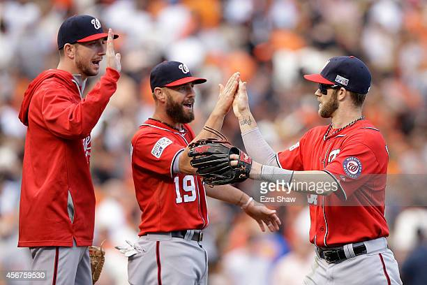 Bryce Harper celebrates with Kevin Frandsen of the Washington Nationals after their 4 to 1 win over the San Francisco Giants during Game Three of the...