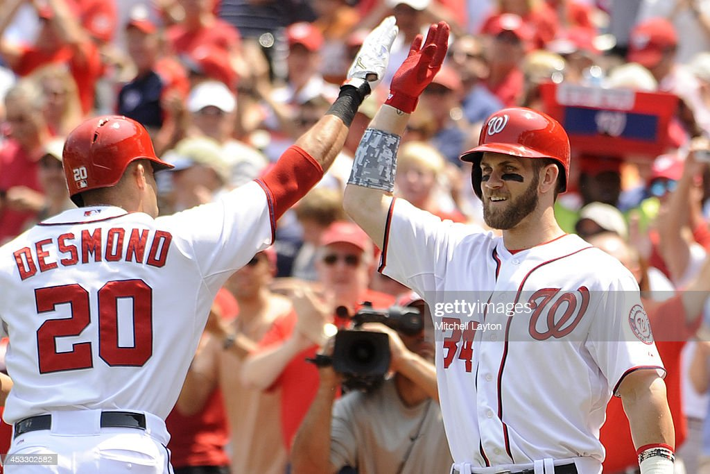 Bryce Harper #34 congratulates Ian Desmond #20 of the Washington Nationals after Desmond hits a two-run home run in the second inning during a baseball game against the New York Mets on August 7, 2014 at Nationals Park in Washington, DC.