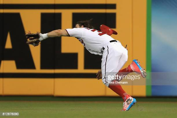 Bryce Harper of the Washington Nationals and the National League catches a ball hit by Salvador Perez of the Kansas City Royals and the American...