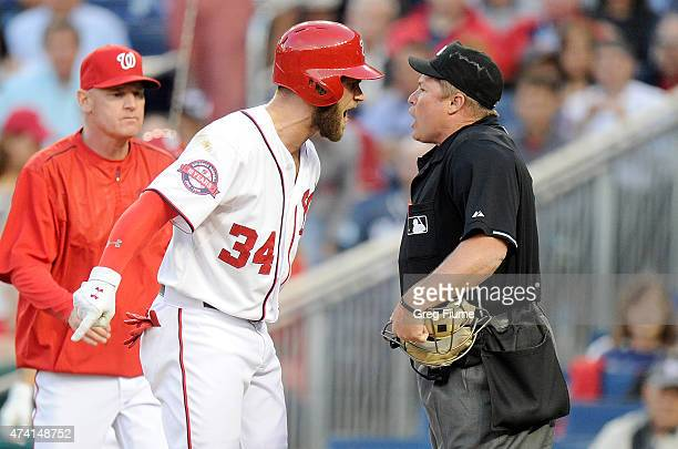 Bryce Harper of the Washington Nationals argues with home plate umpire Marvin Hudson after being thrown out of the game in the third inning against...