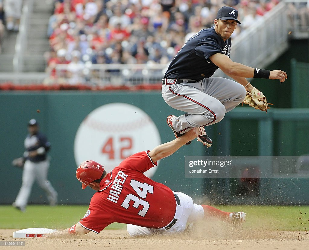 <a gi-track='captionPersonalityLinkClicked' href=/galleries/search?phrase=Bryce+Harper&family=editorial&specificpeople=5926486 ng-click='$event.stopPropagation()'>Bryce Harper</a> #34 of the Washington Nationals attempts to take out Atlanta Braves shortstop Andrelton Simmons (TOP) as Simmons successfully turns a double play, on a grounder by Nationals batter Ryan Zimmerman, during the eighth inning of their game at Nationals Park on June 3, 2012 in Washington, DC.