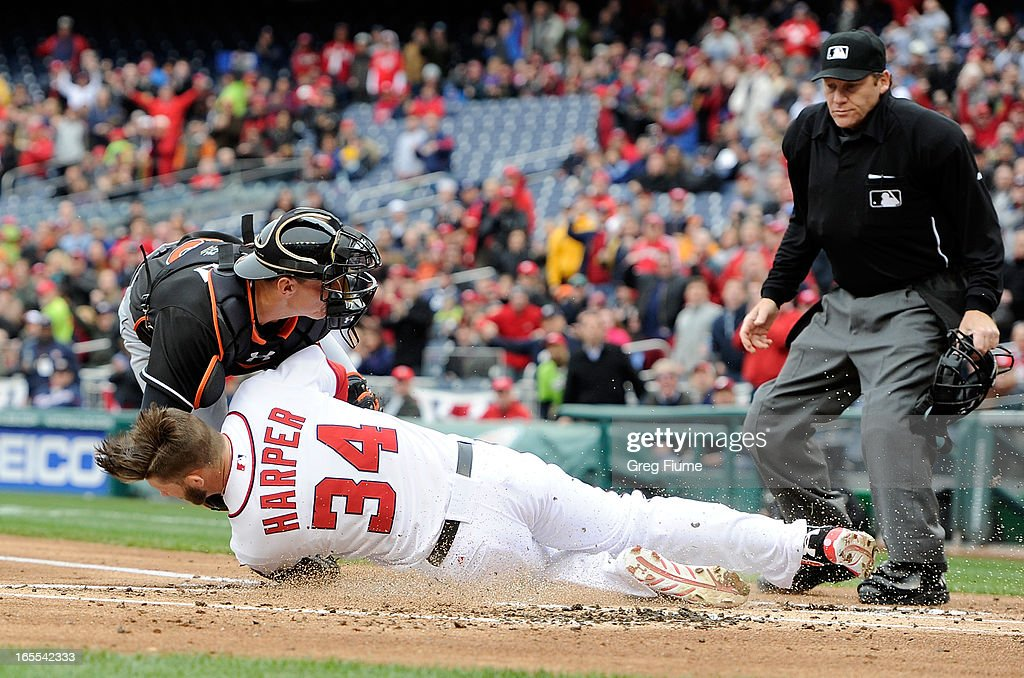 Bryce Harper #34 of the Washington Nationals collides with Rob Brantly #19 of the Miami Marlins while scoring in the first inning at Nationals Park on April 4, 2013 in Washington, DC.