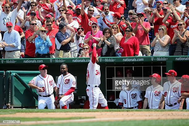 Bryce Harper of the Washington Nationals comes out of the dugout to acknowledge the crowd after hitting a solo home run against the Miami Marlins in...