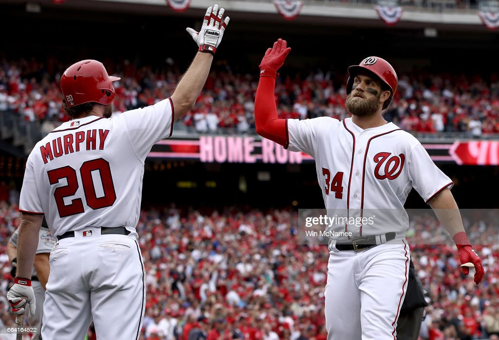 Bryce Harper #34 of the Washington Nationals high fives teammate Daniel Murphy #20 after Harper hit a home run in the sixth inning of the Opening Day game against the Miami Marlins on April 3, 2017 at Nationals Park in Washington, DC.