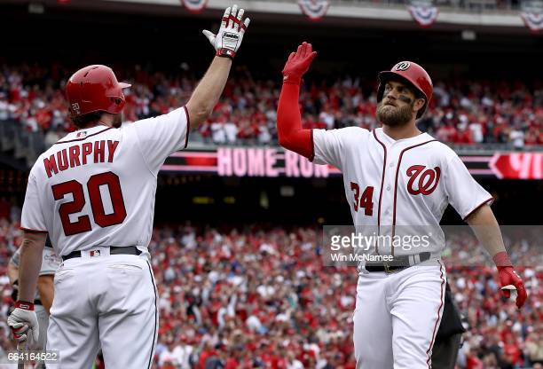 Bryce Harper of the Washington Nationals high fives teammate Daniel Murphy after Harper hit a home run in the sixth inning of the Opening Day game...