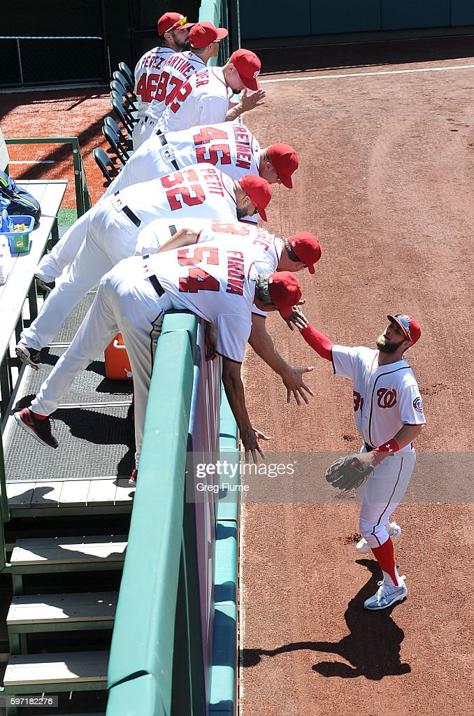 Bryce Harper of the Washington Nationals highfives the pitchers in the bullpen before the game against the Colorado Rockies at Nationals Park on...