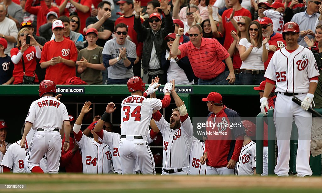 <a gi-track='captionPersonalityLinkClicked' href=/galleries/search?phrase=Bryce+Harper&family=editorial&specificpeople=5926486 ng-click='$event.stopPropagation()'>Bryce Harper</a> #34 of the Washington Nationals is congratulated buy teammates including <a gi-track='captionPersonalityLinkClicked' href=/galleries/search?phrase=Jayson+Werth&family=editorial&specificpeople=206490 ng-click='$event.stopPropagation()'>Jayson Werth</a> #28 after hitting a solo home run in the bottom of the first inning during the Opening Day game against the Miami Marlins at Nationals Park on Monday, April 1, 2013 in Washington, DC. Harper hit two home runs and Washington won the game 2-0.