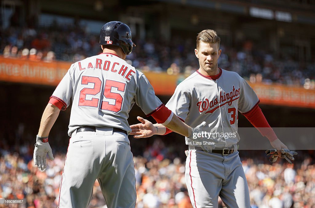 Bryce Harper #34 of the Washington Nationals is congratulated by Adam LaRoche #25 after he scored the go ahead run on a hit by Ian Desmond #20 in the tenth inning of their game against the San Francisco Giants at AT&T Park on May 22, 2013 in San Francisco, California.