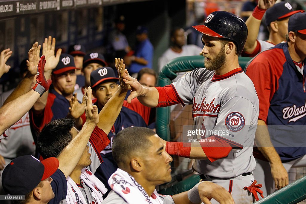 <a gi-track='captionPersonalityLinkClicked' href=/galleries/search?phrase=Bryce+Harper&family=editorial&specificpeople=5926486 ng-click='$event.stopPropagation()'>Bryce Harper</a> #34 of the Washington Nationals is congratulated by teammates in the dugout after scoring a run in the sixth inning of the game against the Philadelphia Phillies at Citizens Bank Park on July 11, 2013 in Philadelphia, Pennsylvania.