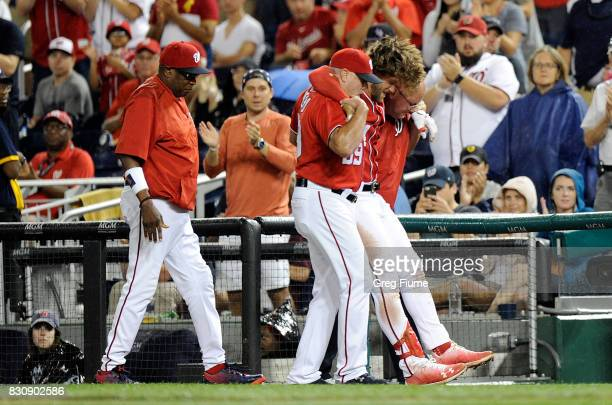 Bryce Harper of the Washington Nationals is helped off the field after injuring his leg in the first inning against the San Francisco Giants at...