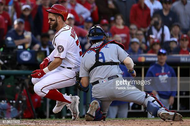 Bryce Harper of the Washington Nationals is tagged out at home plate by Yasmani Grandal of the Los Angeles Dodgers for the third out of the fifth...