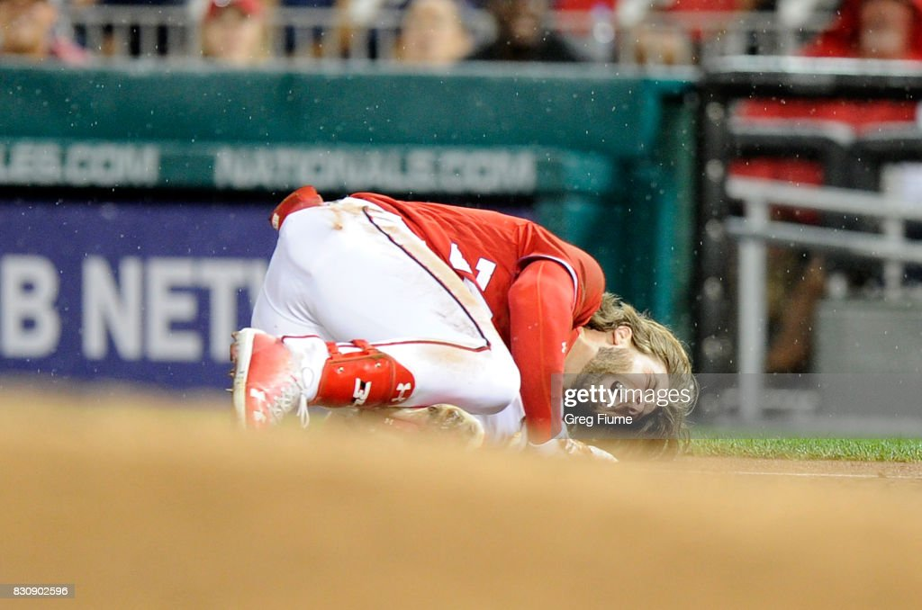 Bryce Harper #34 of the Washington Nationals on the ground in pain after injuring his leg in the first inning against the San Francisco Giants at Nationals Park on August 12, 2017 in Washington, DC.