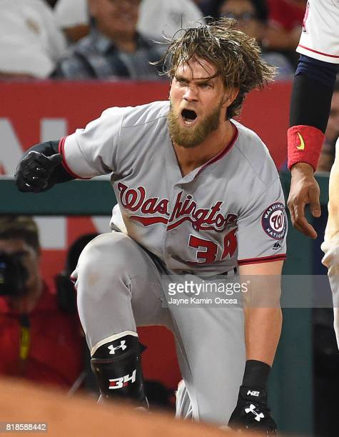 Bryce Harper of the Washington Nationals reacts after he beats the throw to Yunel Escobar of the Los Angeles Angels of Anaheim for a triple in the...