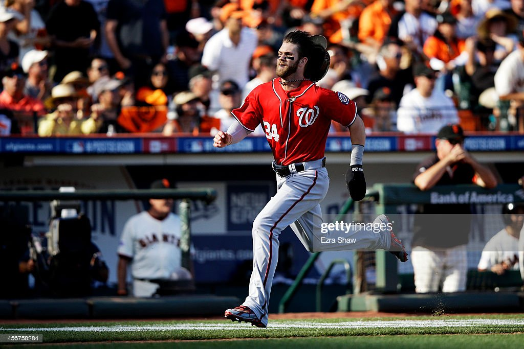 Bryce Harper of the Washington Nationals runs to score on a throwing error by Madison Bumgarner of the San Francisco Giants in the seventh inning...