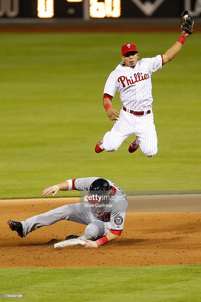 Bryce Harper of the Washington Nationals safely slides to steal second base as Cesar Hernandez of the Philadelphia Phillies jumps to catch the throw...