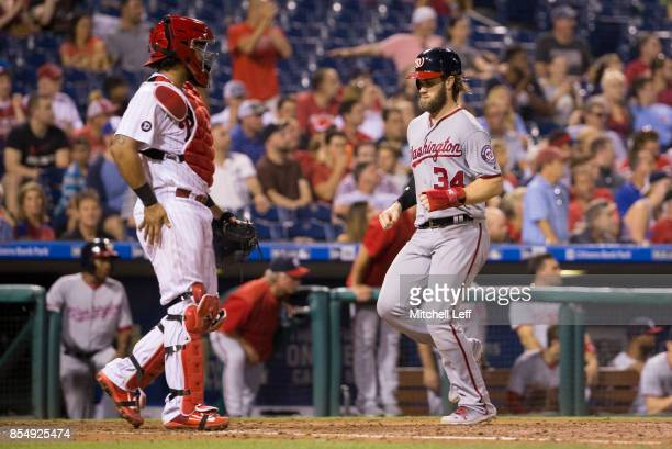 Bryce Harper of the Washington Nationals scores a run in front of Jorge Alfaro of the Philadelphia Phillies in the top of the fifth inning at...