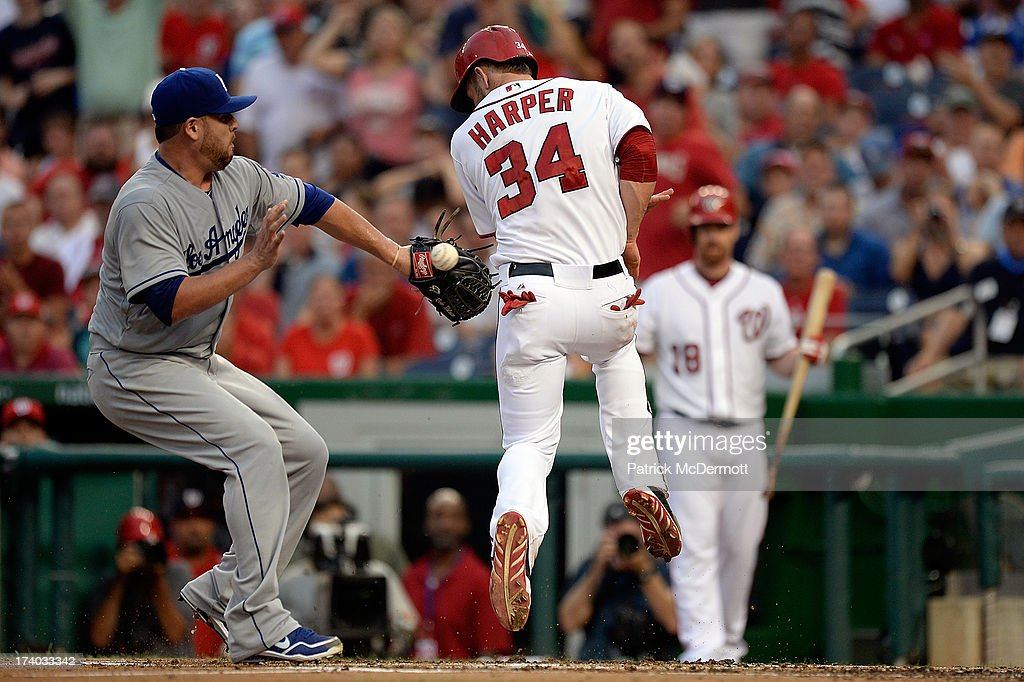 <a gi-track='captionPersonalityLinkClicked' href=/galleries/search?phrase=Bryce+Harper&family=editorial&specificpeople=5926486 ng-click='$event.stopPropagation()'>Bryce Harper</a> #34 of the Washington Nationals scores a run on a wild pitch thrown by starting pitcher <a gi-track='captionPersonalityLinkClicked' href=/galleries/search?phrase=Ricky+Nolasco&family=editorial&specificpeople=600111 ng-click='$event.stopPropagation()'>Ricky Nolasco</a> #47 of the Los Angeles Dodgers in the second inning during a game at Nationals Park on July 19, 2013 in Washington, DC.