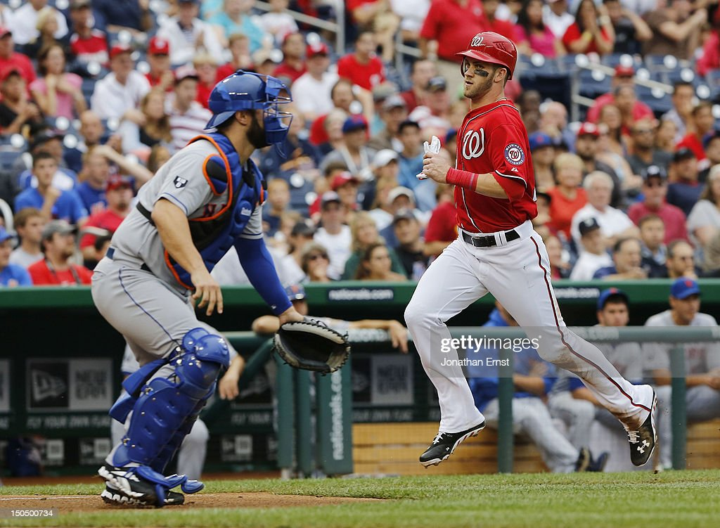 <a gi-track='captionPersonalityLinkClicked' href=/galleries/search?phrase=Bryce+Harper&family=editorial&specificpeople=5926486 ng-click='$event.stopPropagation()'>Bryce Harper</a> #34 of the Washington Nationals scores from third on a single by teammate Ryan Zimmerman (not pictured) as <a gi-track='captionPersonalityLinkClicked' href=/galleries/search?phrase=Kelly+Shoppach&family=editorial&specificpeople=194967 ng-click='$event.stopPropagation()'>Kelly Shoppach</a> #6 of the New York Mets covers the plate during the third inning of their game at Nationals Park on August 19, 2012 in Washington, DC.