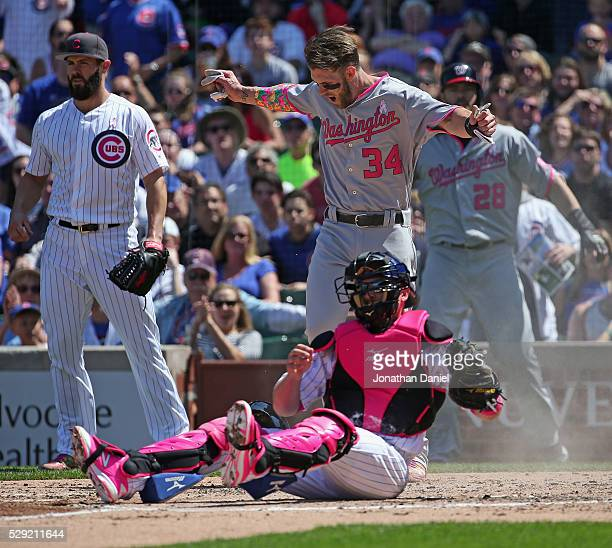 Bryce Harper of the Washington Nationals signals that he's safe after a late tag attempt by Tim Federowicz of the Chicago Cubs in the 3rd inning at...