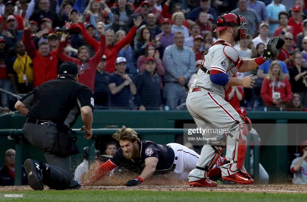 Bryce Harper #34 of the Washington Nationals slides across home plate and scores the game winning run in the tenth inning against the Philadelphia Phillies on April 14, 2017 at Nationals Park in Washington, DC. The Nationals won the game 3-2.