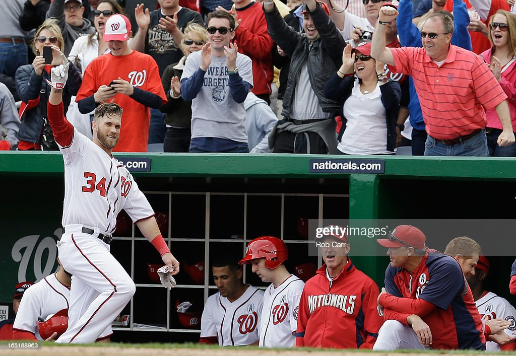 Bryce Harper #34 of the Washington Nationals waves to the crowd after hitting a solo home run against the Miami Marlins during the fourth inning of their opening day game at Nationals Park on April 1, 2013 in Washington, DC.