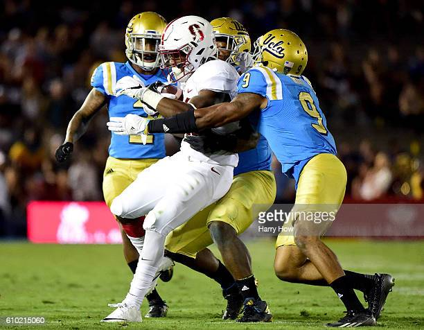 Bryce Love of the Stanford Cardinal is tackled by Jaleel Wadood Jayon Brown and Marcus Rios of the UCLA Bruins during the fourth quarter at Rose Bowl...