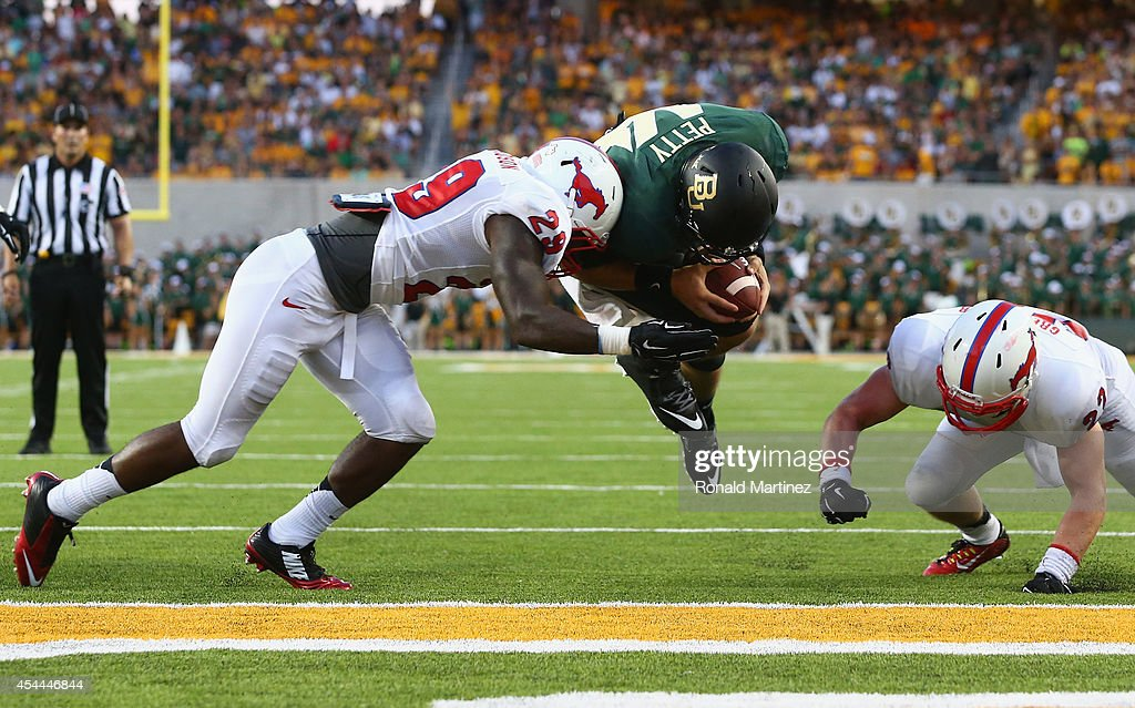 Bryce Petty of the Baylor Bears dives into the endzone for a touchdown against Darrion Richardson of the Southern Methodist Mustangs at McLane...