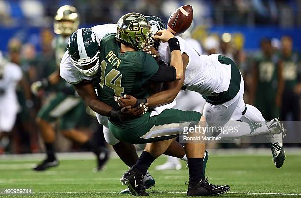 Bryce Petty of the Baylor Bears fumbles as he is hit by Joel Heath of the Michigan State Spartans and Shilique Calhoun of the Michigan State Spartans...