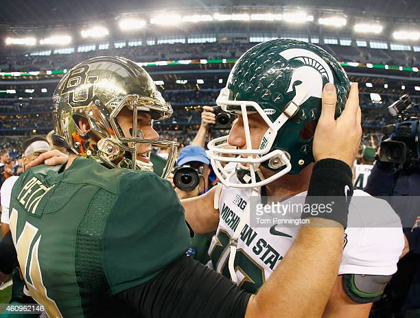 Bryce Petty of the Baylor Bears talks with Connor Cook of the Michigan State Spartans at midfield after the Spartains beat the Bears 4241 during the...