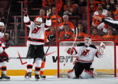 Bryce Salvador and Martin Brodeur of the New Jersey Devils celebrate their 31 victory over the Philadelphia Flyers in Game Five of the Eastern...