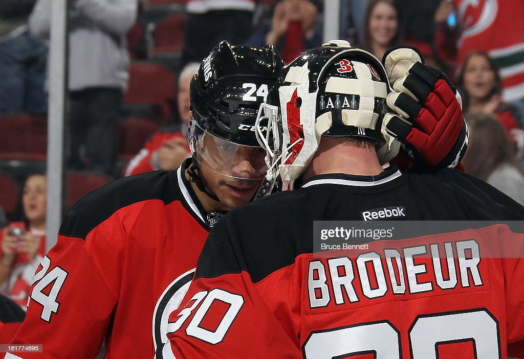 Bryce Salvador #24 congratulates Martin Brodeur #30 of the New Jersey Devils following a victory over the Philadelphia Flyers at the Prudential Center on February 15, 2013 in Newark, New Jersey. The Devils defeated the Flyers 5-3.
