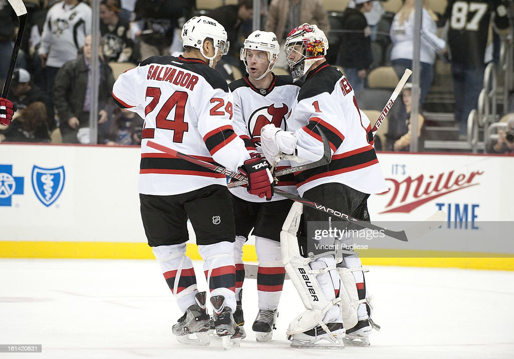 Bryce Salvador # 24 of the New Jersey Devils and Andy Greene # 6 of the New Jersey Devils celebrate with Johan Hedberg # 1 of the New Jersey Devils after their 3-1 victory over the Pittsburgh Penguins on February 10, 2013 at the CONSOL Energy Center in Pittsburgh, Pennsylvania.