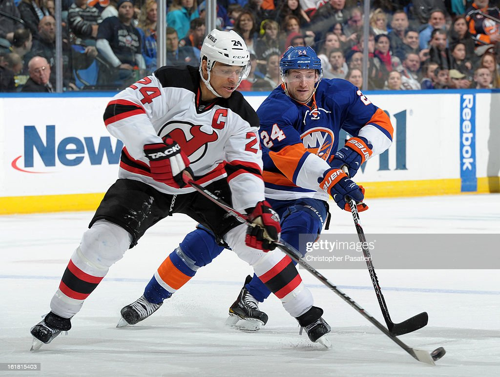 Bryce Salvador #24 of the New Jersey Devils and Brad Boyes #24 of the New York Islanders play for the puck during the game on February 16, 2013 at Nassau Veterans Memorial Coliseum in Uniondale, New York.