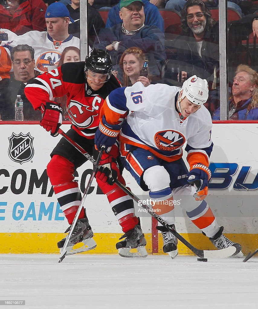Bryce Salvador of the New Jersey Devils and Marty Reasoner of the New York Islanders battle for position on a loose puck during the game at the...