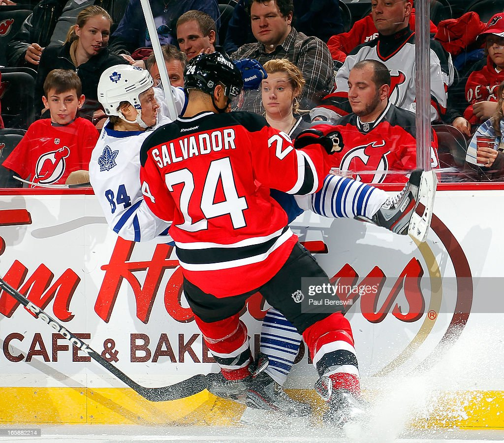 Bryce Salvador #24 of the New Jersey Devils checks John-Michael Liles #24 of the Toronto Maple Leafs during the third period of an NHL hockey game at Prudential Center on April 6, 2013 in Newark, New Jersey. The Leafs won 2-1.