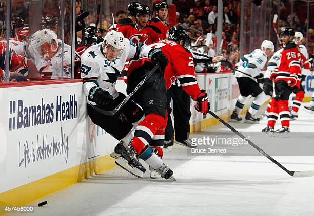 Bryce Salvador of the New Jersey Devils checks Tommy Wingels of the San Jose Sharks into the boards during the first period at the Prudential Center...