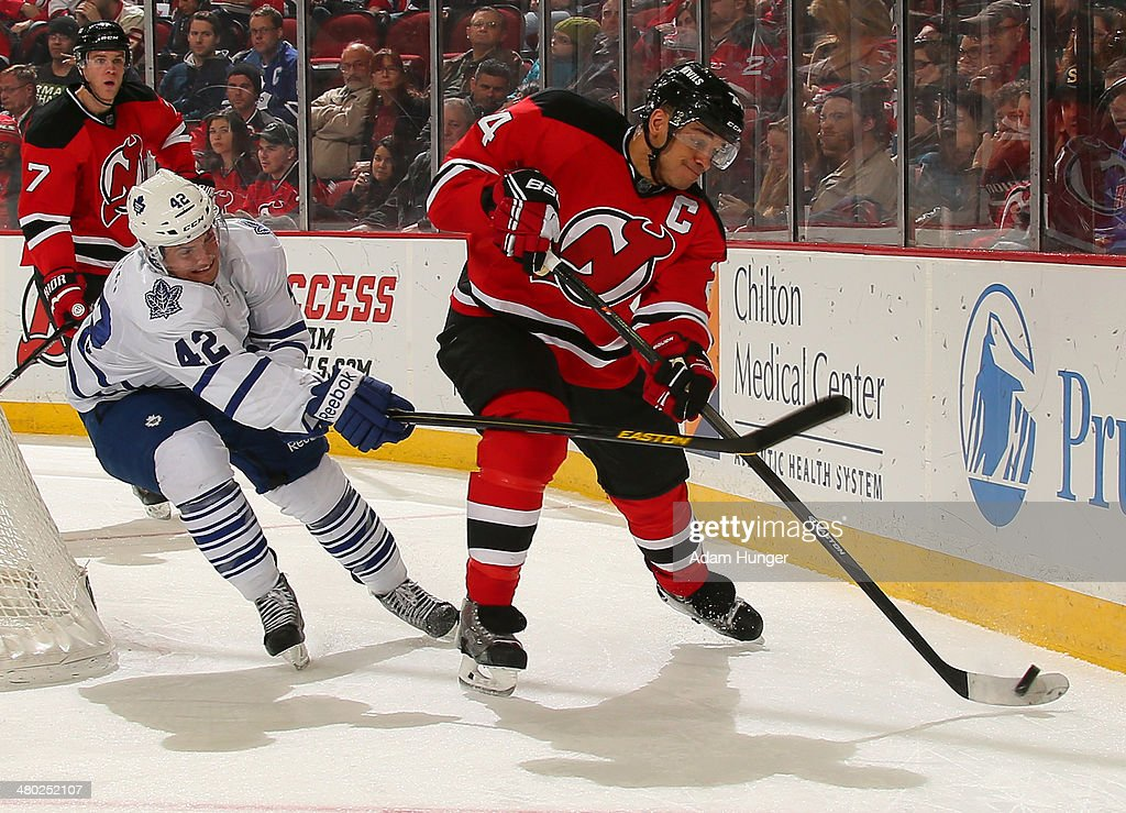 Bryce Salvador #24 of the New Jersey Devils clears the puck defended by Tyler Bozak #42 of the Toronto Maple Leafs during the second period at the Prudential Center on March 23, 2014 in Newark, New Jersey.